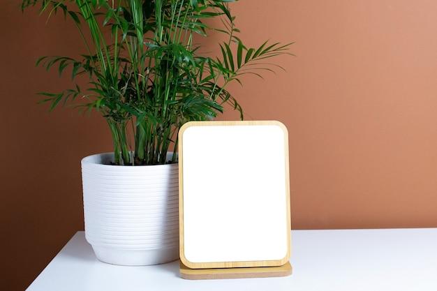 Drewniana rama i zielona roślina na białym stole z ciemnopomarańczowym tle ściany