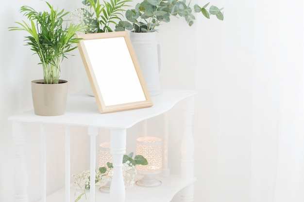 Drewniana rama na vintage białej półce z kwiatami i roślinami