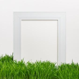 Drewniana rama na zielonej naturalnej trawie. wiosenny nastrój. koncepcja świąt wielkanocnych. skopiuj miejsce