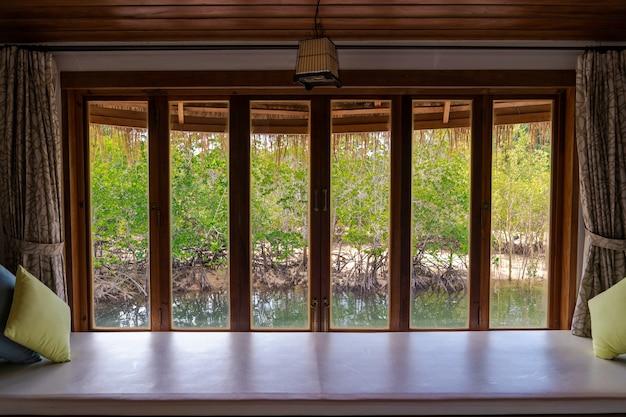 Drewniana rama okienna z przezroczystymi okularami nad siedzeniem relaksacyjnym z widokiem na zielony las namorzynowy