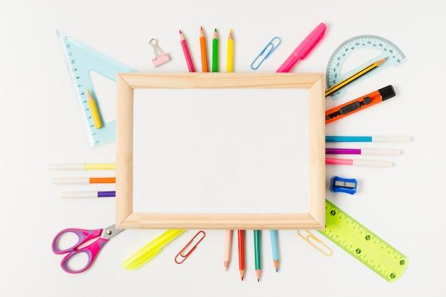 Drewniana rama otoczona szkolnymi akcesoriami