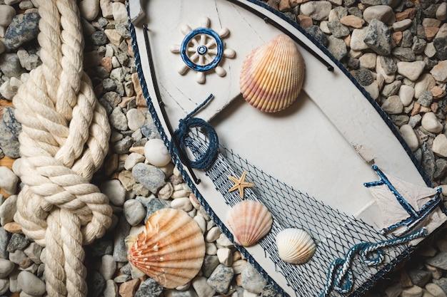 Drewniana rama ozdobiona muszlami i linami leżącymi na kamieniach na brzegu