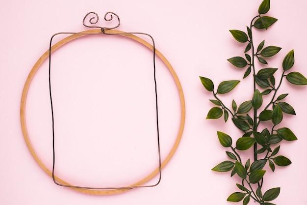 Drewniana rama w pobliżu sztucznej rośliny zielonej na różowym tle