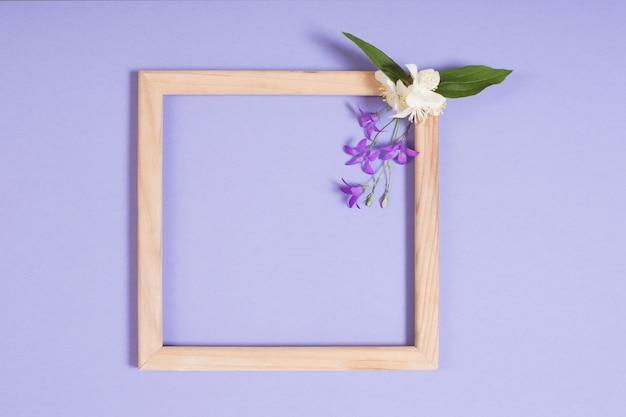 Drewniana rama z kwiatami na fioletowym papierze