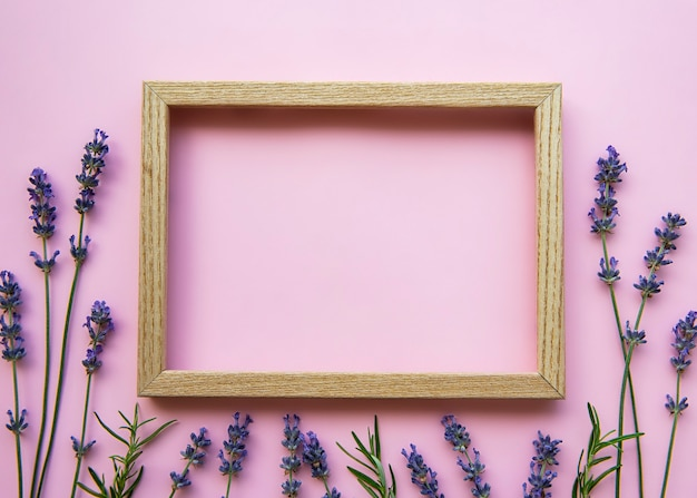 Drewniana rama z pięknymi kwiatami pachnącej lawendy na różowym tle