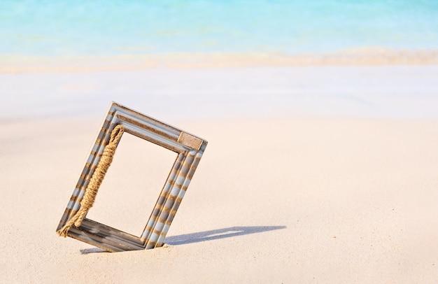 Drewniana ramka na zdjęcia na tropikalnym morskim piasku i tle plaży z miejscem na kopię