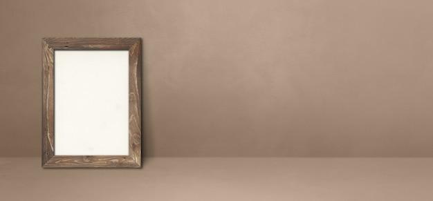 Drewniana ramka na zdjęcia oparta na beżowej ścianie. pusty szablon makiety. baner poziomy