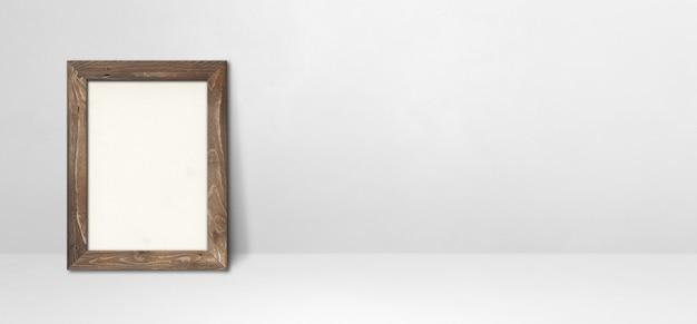 Drewniana ramka na zdjęcia oparta na białej ścianie. pusty szablon makiety. baner poziomy