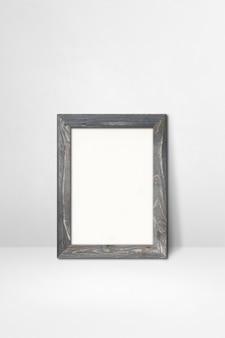Drewniana ramka na zdjęcia oparta na białej ścianie. pusty szablon makiety