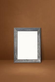 Drewniana ramka na zdjęcia oparta na brązowej ścianie. pusty szablon makiety