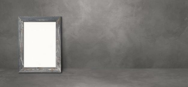 Drewniana ramka na zdjęcia oparta na ciemnej betonowej ścianie. pusty szablon makiety. baner poziomy