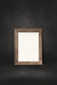 Drewniana ramka na zdjęcia oparta na czarnej ścianie. szablon makiety prezentacji