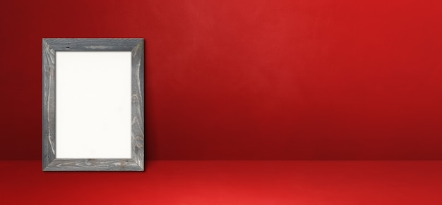 Drewniana ramka na zdjęcia oparta na czerwonej ścianie. pusty szablon makiety. baner poziomy