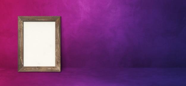 Drewniana ramka na zdjęcia oparta na fioletowej ścianie. pusty szablon makiety. baner poziomy