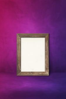 Drewniana ramka na zdjęcia oparta na fioletowej ścianie. pusty szablon makiety