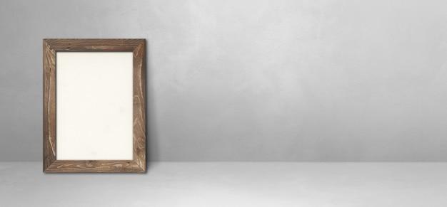 Drewniana ramka na zdjęcia oparta na jasnoszarej ścianie. pusty szablon makiety. baner poziomy