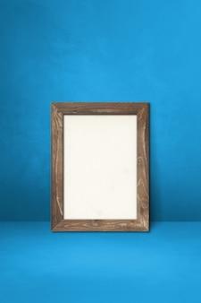 Drewniana ramka na zdjęcia oparta na niebieskiej ścianie. pusty szablon makiety