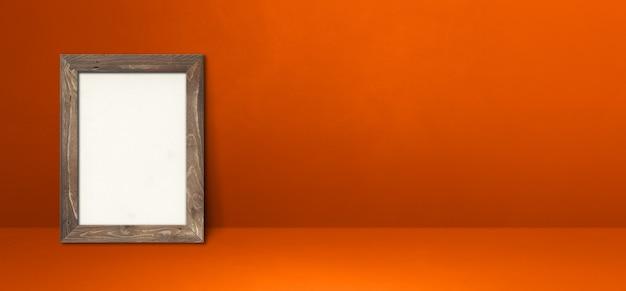 Drewniana ramka na zdjęcia oparta na pomarańczowej ścianie. pusty szablon makiety. baner poziomy