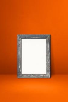 Drewniana ramka na zdjęcia oparta na pomarańczowej ścianie. pusty szablon makiety