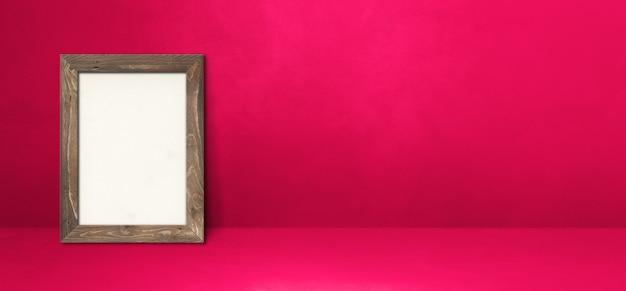 Drewniana ramka na zdjęcia oparta na różowej ścianie. pusty szablon makiety. baner poziomy