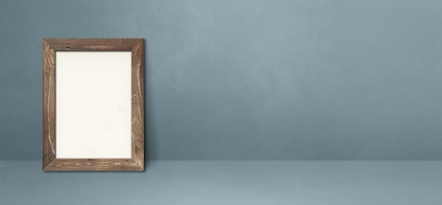 Drewniana ramka na zdjęcia oparta na szarej ścianie. pusty szablon makiety. baner poziomy