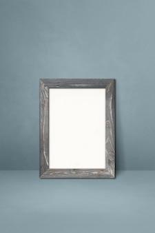 Drewniana ramka na zdjęcia oparta na szarej ścianie. pusty szablon makiety