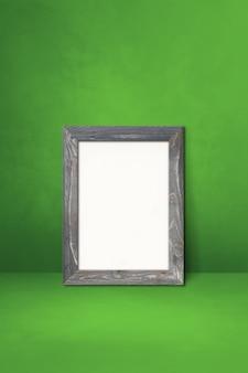 Drewniana ramka na zdjęcia oparta na zielonej ścianie. pusty szablon makiety
