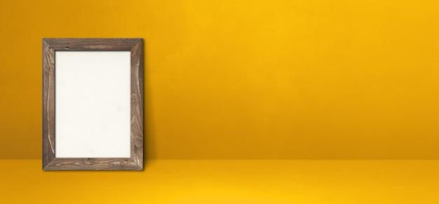 Drewniana ramka na zdjęcia oparta na żółtej ścianie. pusty szablon makiety. baner poziomy