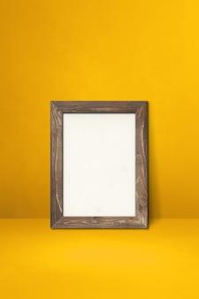 Drewniana ramka na zdjęcia oparta na żółtej ścianie. pusty szablon makiety