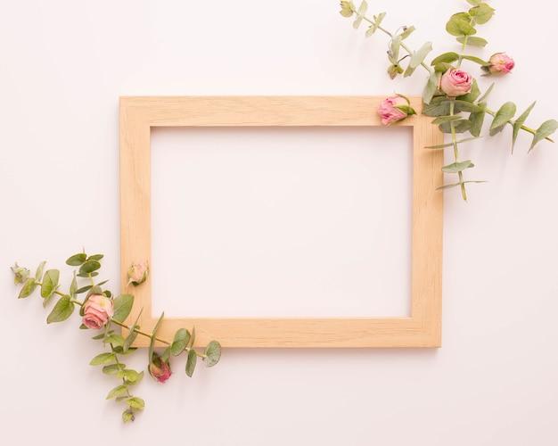 Drewniana ramka na zdjęcia ozdobiona różowymi różami i eukaliptusem