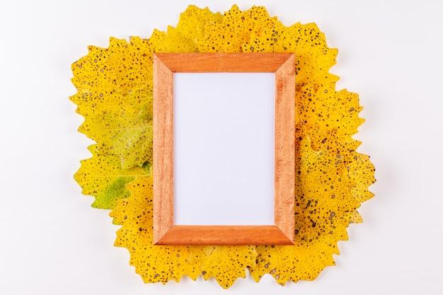 Drewniana ramka na zdjęcia w stylu jesieni z białym copyspace otoczony żółtymi liśćmi