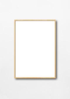 Drewniana ramka na zdjęcia wisząca na białej ścianie.