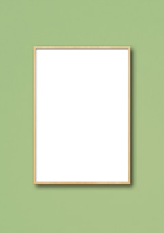 Drewniana ramka na zdjęcia wisząca na jasnozielonej ścianie.