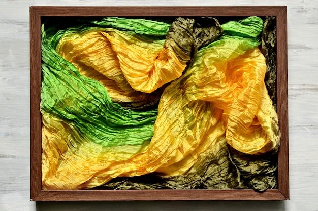 Drewniana ramka na zdjęcia wypełniona tkaniną jedwabną w kolorach żółtym, zielonym i brązowym