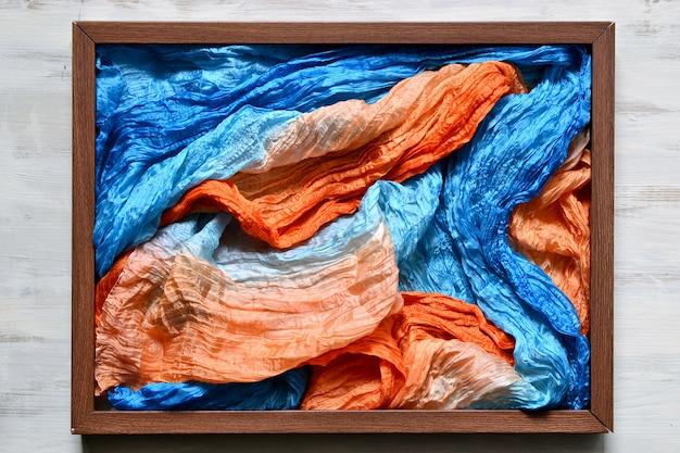 Drewniana ramka na zdjęcia wypełniona tkaniną z jedwabną tkaniną w kolorze niebieskim i pomarańczowym
