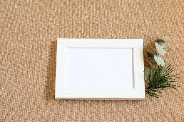 Drewniana ramka na zdjęcia z białymi półfabrykatami na ekologicznym płótnie teksturowanym. makieta zdjęcia.