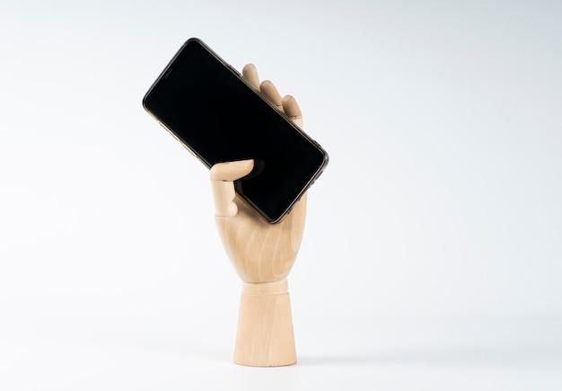 Drewniana ręka chwytająca telefon