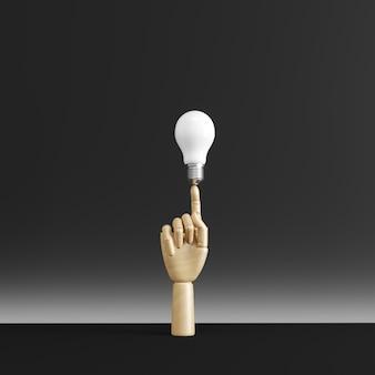 Drewniana ręka palec wskazujący na białą żarówkę.