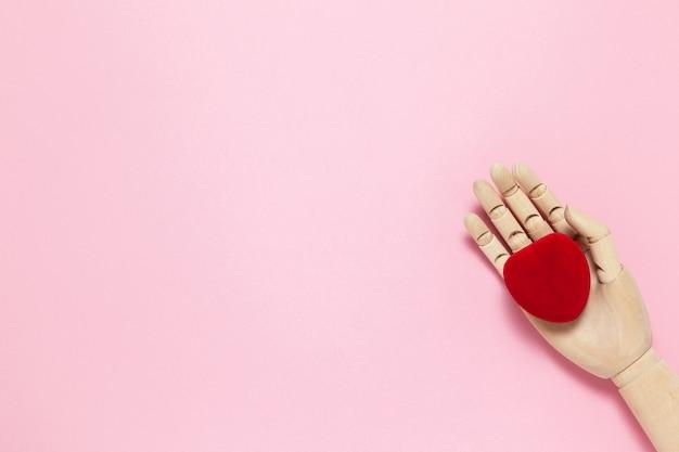 Drewniana ręka trzyma czerwone małe aksamitne pudełko w kształcie serca na biżuterię na różowym tle, miejsce na kopię, płaskie ułożenie. 8 marca, 14 lutego, urodziny, walentynki, matka, koncepcja obchodów dnia kobiet.
