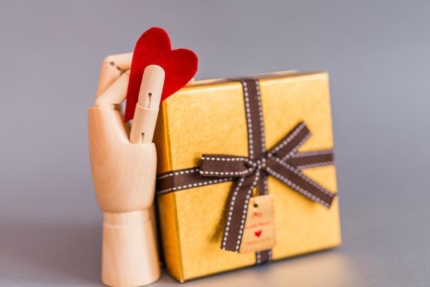 Drewniana ręka trzyma czerwonego kierowego pobliskiego prezenta pudełko