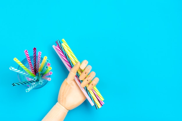 Drewniana ręka trzymać słomki do picia w paski na imprezę w szkle na niebieskim tle.