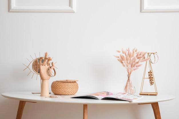 Drewniana ręka z biżuterią żeńską na stole we wnętrzu pokoju