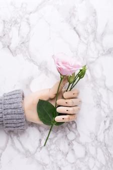 Drewniana ręka z kwiatkiem na marmurze