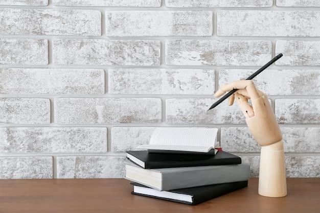 Drewniana ręka z ołówkiem i zeszytami na stole