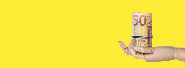 Drewniana ręka z pieniędzmi na białym tle na żółtym tle. banknoty euro zwinięte w tubę. rolka banknotów 50 euro, z miejscem na kopię. długi, szeroki baner. skopiuj miejsce na swój projekt.