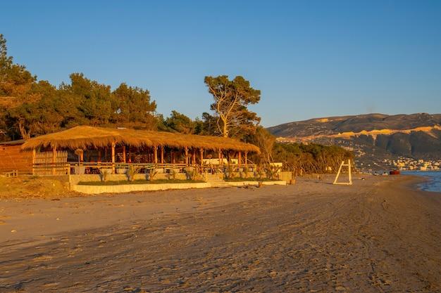 Drewniana restauracja na plaży na tle błękitnego morza i nieba
