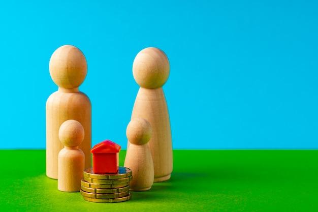 Drewniana rodzina z domu zabawki i stos monet. oszczędności na zakup domu