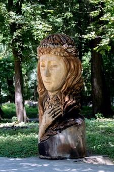 Drewniana rzeźba przedstawiająca kobietę o wyglądzie słowiańskim w parku miejskim