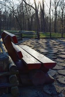 Drewniana rzeźbiona ławka parkowa wykonana z grubych bali w letnim lesie z pokryciem drewnianym