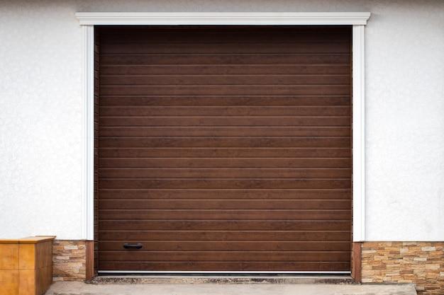 Drewniana ściana nowoczesnego wiejskiego garażu z automatyczną podnoszoną bramą.